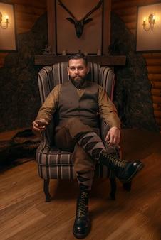 Homme chasseur en vêtements traditionnels britanniques assis sur une chaise après la chasse et boire du whisky.