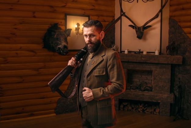 Homme chasseur en vêtements vintage avec fusil antique