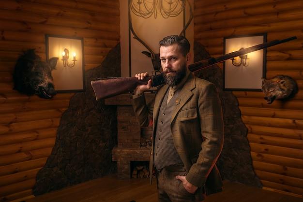 Homme chasseur avec une vieille arme contre la poitrine antique