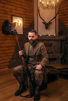 Homme chasseur avec une vieille arme à feu dans des vêtements de chasse traditionnels de style rétro assis sur un coffre antique.
