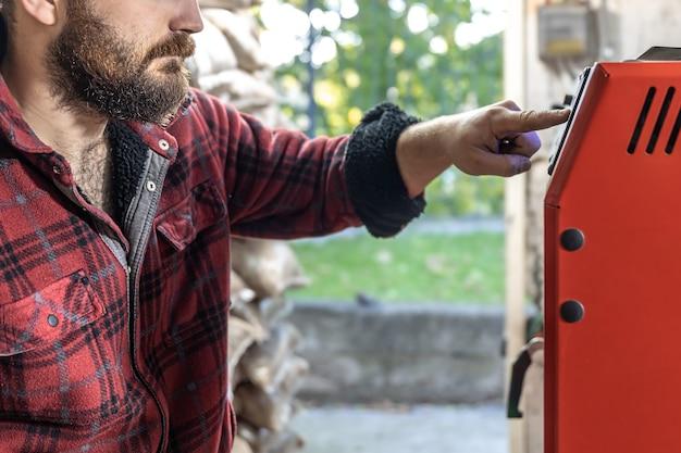 L'homme avec une chaudière à combustible solide travaillant avec un chauffage économique aux biocarburants