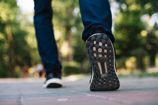 Homme en chaussures de sport marchant dans une allée