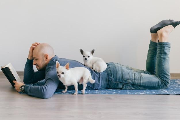 Homme chauve adulte dans des vêtements à la mode allongé sur un tapis de yoga, livre de lecture avec deux chiots chihuahua allongé sur lui.