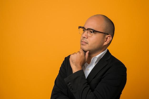 Homme chauve d'affaires portant des lunettes chercher en touchant son menton avec la main isolé sur jaune