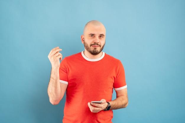 Un homme chauve d'âge moyen avec une barbe dans un t-shirt rouge sur fond bleu se tient debout avec ses bras montre à quel point tout est simple. isolé.