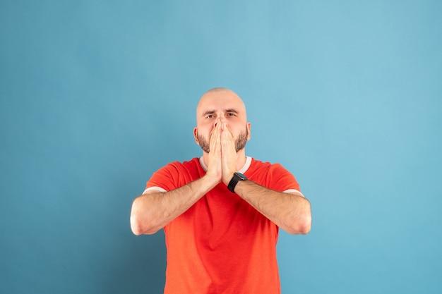Un homme chauve d'âge moyen avec une barbe et un t-shirt rouge, craintivement, se couvre le visage avec ses mains.