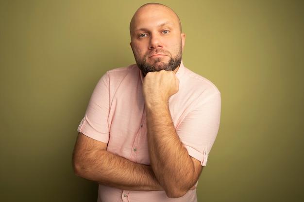 Homme chauve d'âge moyen confiant portant un t-shirt rose mettant la main sous le menton isolé sur vert olive