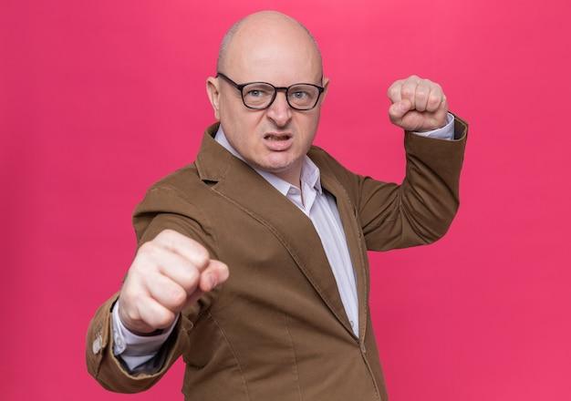 Homme chauve d'âge moyen en costume portant des lunettes à l'avant avec le visage en colère avec les poings fermés va se battre debout sur le mur rose