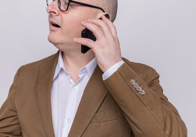 Homme chauve d'âge moyen en costume portant des lunettes souriant heureux et positif tout en parlant au téléphone mobile