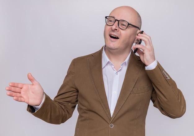 Homme chauve d'âge moyen en costume portant des lunettes souriant largement heureux et joyeux tout en parlant au téléphone mobile debout sur un mur blanc