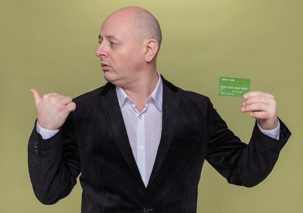 Homme chauve d'âge moyen en costume tenant une carte de crédit à côté pointant vers l'arrière avec un pouce debout sur un mur vert