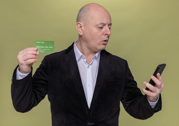 Homme chauve d'âge moyen en costume tenant une carte de crédit à la recherche de téléphone mobile à être confus debout sur mur vert