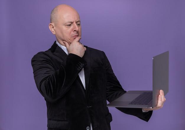 Homme chauve d'âge moyen en costume tenant un ordinateur portable en regardant l'écran avec une expression pensive sur le visage pensant debout sur le mur violet