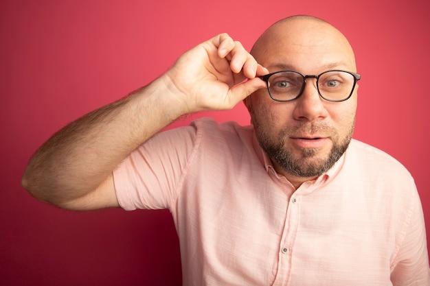 Homme chauve d'âge moyen suspect portant t-shirt rose portant et tenant des lunettes isolé sur mur rose