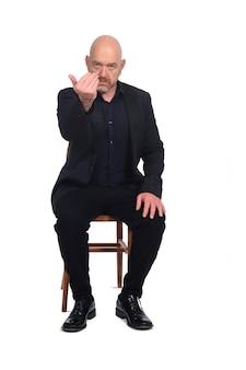 Homme chauve assis sur une chaise qui invite