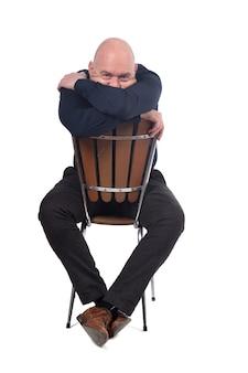 Homme chauve assis sur fond blanc, couvre son visage avec ses bras