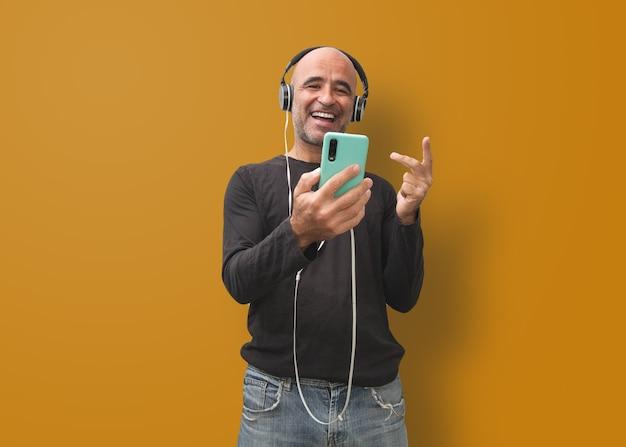 Homme chauve attirant écoutant la musique avec le voleur d'écouteurs