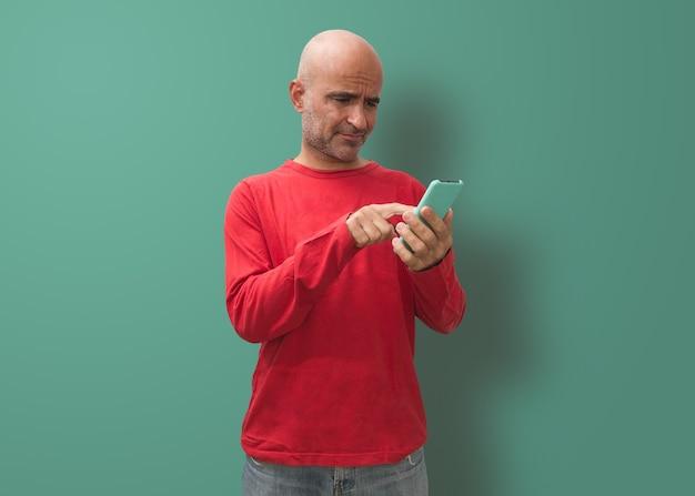 Homme chauve attirant manipulant le périphérique mobile