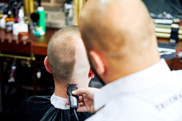 Homme chauve au salon de coiffure