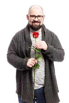 Un homme chauve avec une barbe tient une rose rouge dans ses mains. isolé sur mur blanc. verticale.