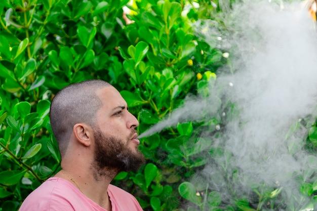 Homme chauve et barbu fumant