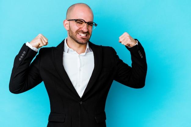 Homme chauve caucasien jeune entreprise sur bleu levant le poing après une victoire, concept gagnant.