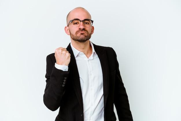 Homme chauve caucasien jeune entreprise sur bleu montrant le poing, expression faciale agressive.