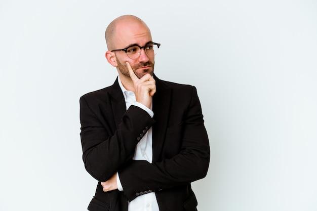Homme chauve caucasien jeune entreprise isolé sur bleu contemplant, planifiant une stratégie, réfléchissant à la manière d'une entreprise
