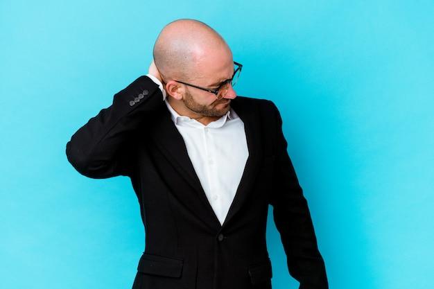 Homme chauve caucasien jeune entreprise isolé sur fond bleu ayant une douleur au cou due au stress, en massant et en le touchant avec la main.