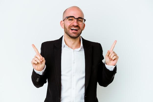 Homme chauve caucasien jeune entreprise isolé sur fond bleu pointant vers différents espaces de copie, en choisissant l'un d'entre eux, montrant avec le doigt.