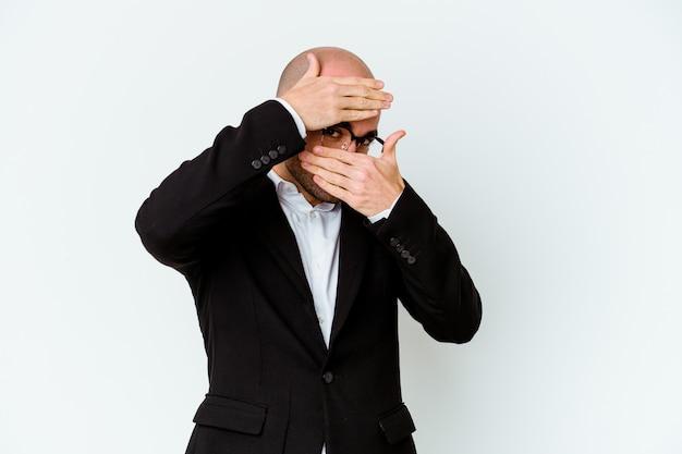 Homme chauve caucasien jeune entreprise isolé sur un mur bleu clignote à travers les doigts, visage couvrant embarrassé.