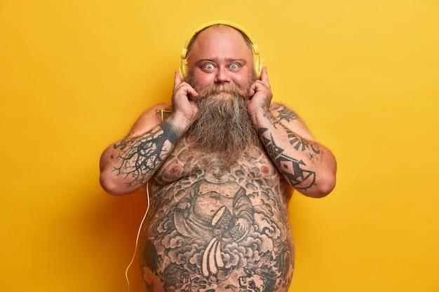 Un homme chauve choqué avec un corps obèse nu, a les bras et le ventre tatoués, une barbe épaisse, des frissons avec de bonnes vibrations, écoute de la musique dans des écouteurs, bénéficie d'un son exceptionnel, isolé sur un mur jaune.