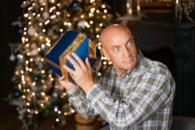 L'homme chauve drôle écoute une boîte avec un cadeau sur le fond d'un arbre de noël