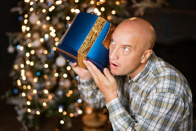 L'homme chauve drôle écoute une boîte avec un cadeau sur le mur d'un arbre de noël