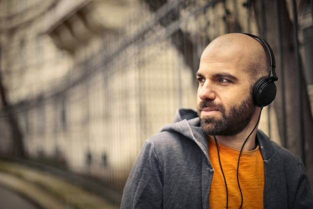 Homme chauve en écoutant de la musique sur des écouteurs