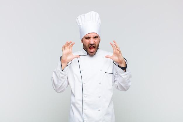Homme chauve hurlant de panique ou de colère, choqué, terrifié ou furieux, les mains à côté de la tête
