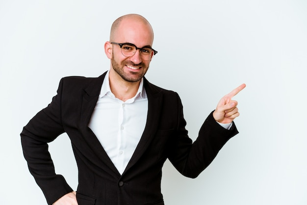 Homme chauve jeune entreprise isolé sur mur bleu souriant joyeusement pointant avec l'index loin