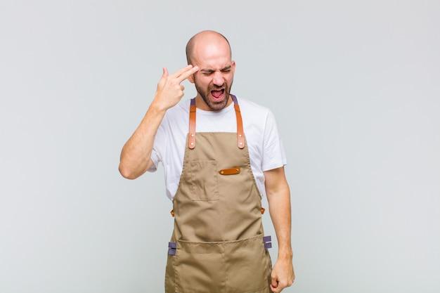 Homme chauve à la malheureuse et stressée, geste de suicide faisant signe des armes à feu avec la main, pointant vers la tête