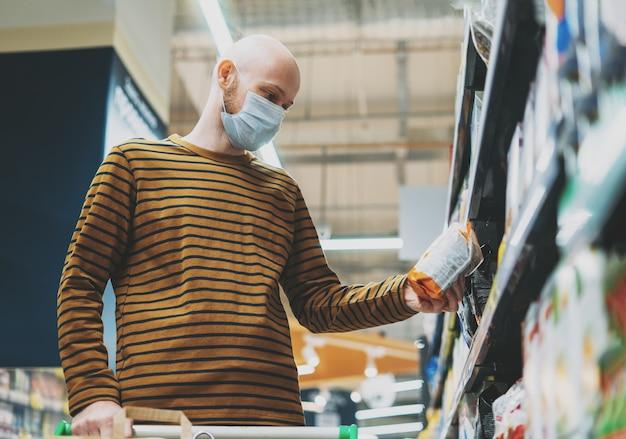 Un homme chauve en masque médical choisit des produits dans le supermarché, concept de quarantaine de coronavirus