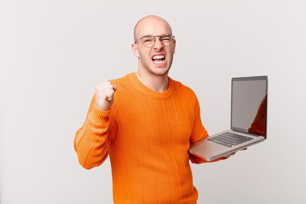 Homme chauve avec ordinateur criant agressivement avec une expression de colère ou avec les poings serrés célébrant le succès