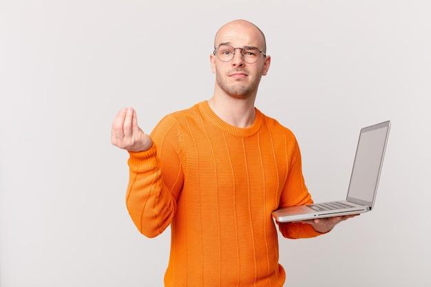 Homme chauve avec un ordinateur faisant un geste de capice ou d'argent, vous disant de payer vos dettes!