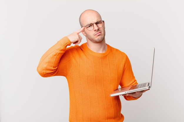 Homme chauve avec ordinateur se sentant confus et perplexe, montrant que vous êtes fou, fou ou fou