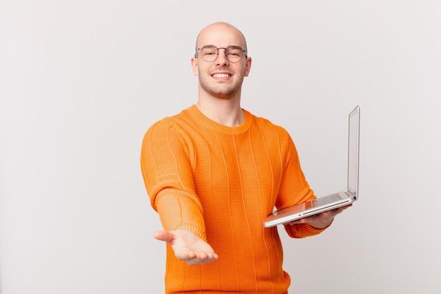 Homme chauve avec ordinateur souriant joyeusement avec un regard amical, confiant et positif, offrant et montrant un objet ou un concept