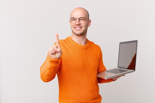 Homme chauve avec ordinateur souriant et semblant amical, montrant le numéro un ou le premier avec la main en avant, compte à rebours