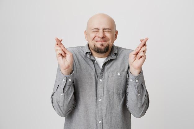 Un homme chauve plein d'espoir croise les doigts, faisant un vœu les yeux fermés