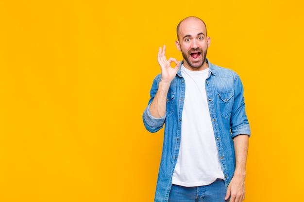 Homme chauve se sentant réussi et satisfait, souriant avec la bouche grande ouverte, faisant signe correct avec la main