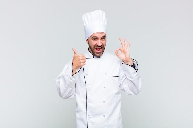 Homme chauve se sentir heureux, étonné, satisfait et surpris, montrant des gestes corrects et des pouces vers le haut, souriant