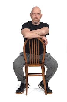 Homme chauve sérieux avec des vêtements de sport assis sur fond blanc