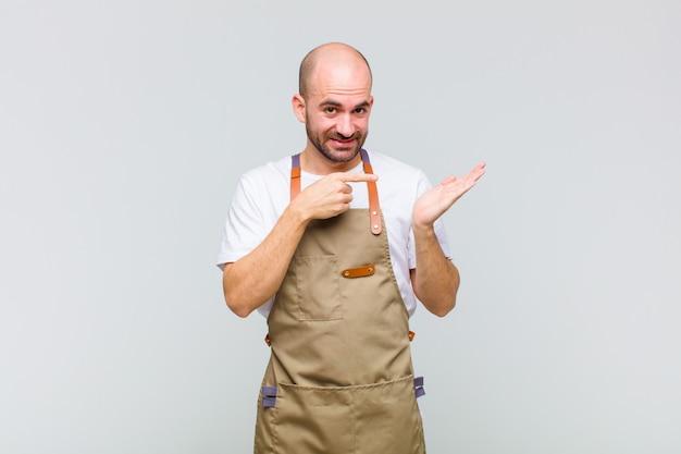 Homme chauve souriant joyeusement et pointant vers l'espace de copie sur la paume sur le côté, montrant ou annonçant un objet