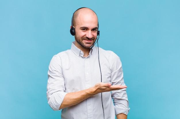 Homme chauve souriant joyeusement, se sentir heureux et montrant un concept dans l'espace de copie avec la paume de la main